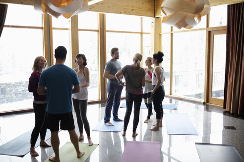 People talking after yoga class in studio - HEROF10882