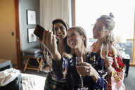 Happy women friends drinking champagne and taking selfie in hotel room, enjoying spa weekend - HEROF10933