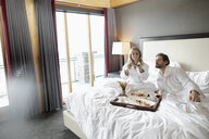 Couple in bathrobes eating breakfast in bed in luxury hotel room, enjoying romantic weekend - HEROF10957