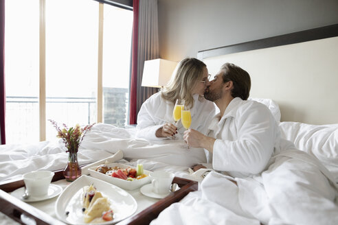 Affectionate couple in bathrobes kissing, drinking mimosas in hotel bed, enjoying romantic weekend - HEROF10960