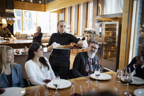 Waitress serving tray of food to business people dining at restaurant table - HEROF11011