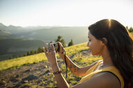 Woman with digital camera photographing sunny mountain view, Alberta, Canada - HEROF11065