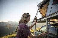 Woman camping, climbing up to SUV rooftop tent in idyllic mountain field, Alberta, Canada - HEROF11071