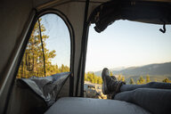Woman relaxing in SUV rooftop tent in idyllic mountain field, Alberta, Canada - HEROF11074