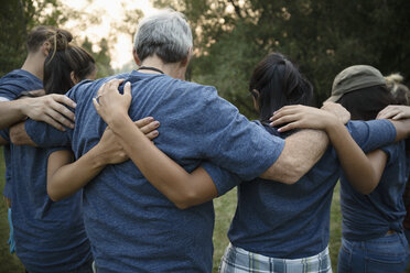 Volunteers hugging in huddle - HEROF11101