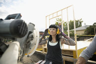 Woman with tattoos and ear protectors standing at saw at construction site - HEROF11128