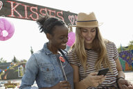 Young women with smart phone at kissing booth - HEROF11158