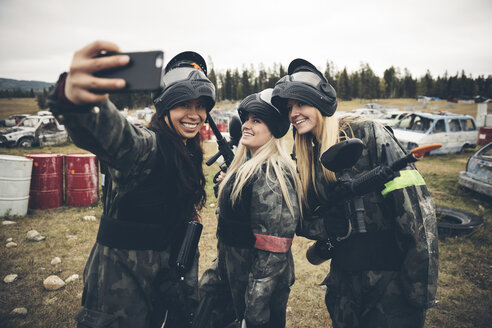 Women friends paintballing, taking selfie in field - HEROF11188