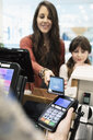 Woman making smart phone contactless payment in shop - HEROF11218