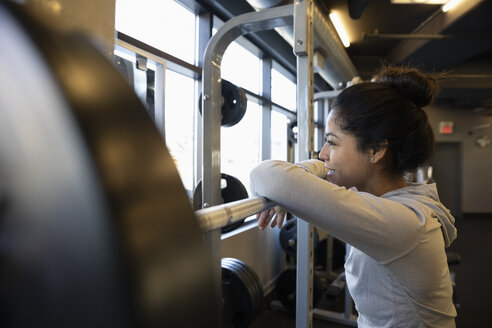Woman exercising, resting on barbell in gym - HEROF11230