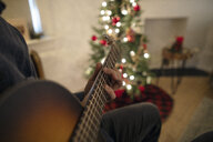 Close up man playing guitar in Christmas living room - HEROF11284