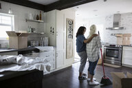 Affectionate daughter with senior mother, downsizing, packing and sweeping kitchen - HEROF11287