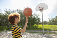 Cool teenage girl with afro balancing basketball on finger at park basketball court - HEROF11311