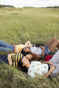 Carefree teenage girl friends laying in tall grass - HEROF11314
