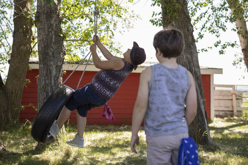 Brothers playing on tire swing - HEROF11317