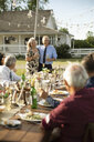 Affectionate couple celebrating anniversary, toasting friends at garden party table - HEROF11329