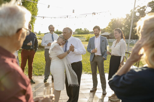Affectionate senior bride and groom dancing in sunny rural garden - HEROF11332