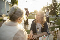 Affectionate friend talking with senior bride at table in sunny rural garden - HEROF11350