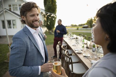Couple drinking champagne, talking at wedding reception in rural garden - HEROF11353