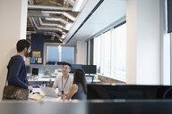 Business people using laptop, talking in open plan office - HEROF11395