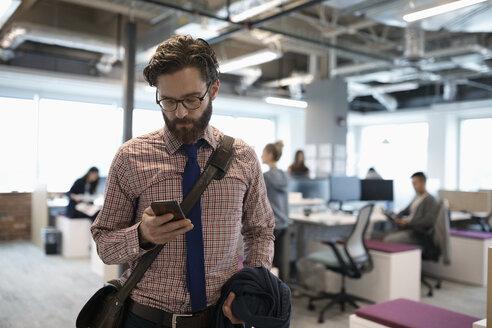 Businessman using smart phone, leaving office - HEROF11401