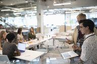 Businessmen using laptop, talking in conference room meeting - HEROF11428