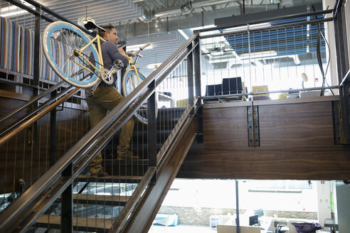 Businessman carrying bicycle up office stairs - HEROF11437