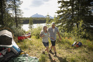Affectionate mature couple at sunny forest campsite, Alberta, Canada - HEROF11446