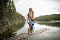 Affectionate, serene mature couple standing on diving board above lake, Alberta, Canada - HEROF11449