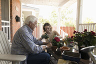 Daughter helping senior father planting flowers on porch - HEROF11479