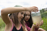 Curious girl friends looking at frog in jar - HEROF11548