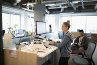 Creative businesswoman standing at desk, using laptop and computer in open plan office - HEROF11602