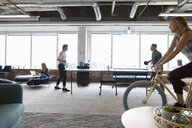 Creative businesswoman riding bicycle and businessmen playing ping pong in open plan office - HEROF11617