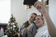 Happy young couple with smart phone taking selfie with Christmas gift - HEROF11626