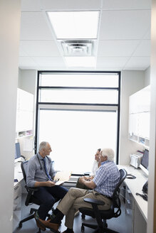 Male doctor with medical record talking to senior patient with daughter in clinic office - HEROF11692