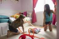 Girl friends playing with toy car track in bedroom - HEROF11698