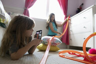 Girl friends with camera phone playing with toy car track in bedroom - HEROF11701