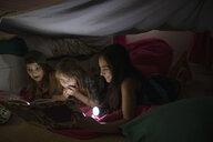Girl friends reading book with flashlight in dark bedroom fort, enjoying sleepover - HEROF11713