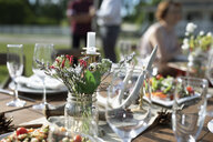 Flowers, food and placesettings on sunny patio table - HEROF11740