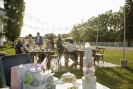 Friends celebrating behind tiered wedding cake, gifts and flowers on patio table - HEROF11752