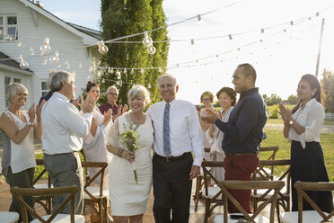 Friends clapping for senior bride and groom getting married in rural garden - HEROF11755