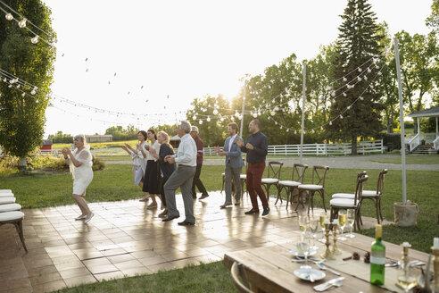 Friends dancing, celebrating at wedding reception in rural garden - HEROF11758