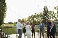 Friends and senior bride and groom clapping at wedding reception in rural garden - HEROF11761