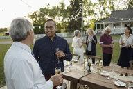 Male friends talking, drinking champagne at wedding reception in rural garden - HEROF11764