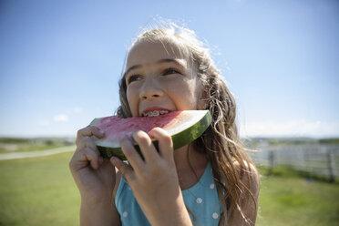 Happy girl with braces eating watermelon on sunny farm - HEROF11770