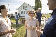 Friends talking, drinking wine at wedding reception in sunny rural garden - HEROF11773