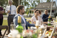 Friends drinking and eating, enjoying wedding reception lunch in rural garden - HEROF11776