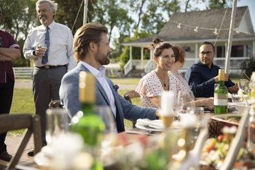 Friends drinking and eating, enjoying wedding reception lunch in rural garden - HEROF11776