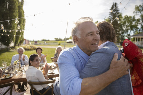 Grateful father hugging son at retirement party in rural garden with friends - HEROF11788