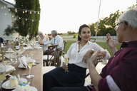 Friends talking and drinking champagne at wedding reception table in rural garden - HEROF11803